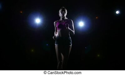 Approaching shooting running girl backlit on black background. Slow motion. Close up