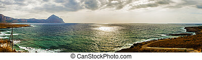 Approaching storm on a beach of Sicily. The sun filters through a hole in the clouds and stormy