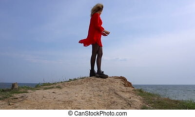Approaching to Happy Young Woman in Red Dress Have Fun at the Sea Coast Cliff