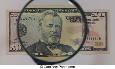 Approaching using a magnifying glass fifty dollar bill. The...