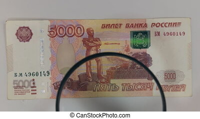 Approaching using a magnifying glass five-thousandth ruble bill. The concept of finance