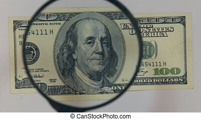 Approaching using a magnifying glass hundred dollar bill....