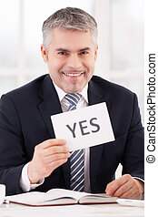 Approved! Cheerful grey hair man in formalwear holding a paper with yes sign on it while sitting at her working place