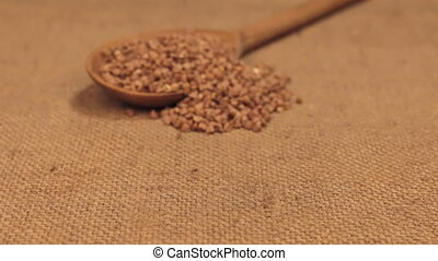 Approximation of a wooden spoon overflowing with buckwheat grains, lying on burlap.
