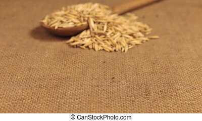 Approximation of a wooden spoon overflowing with oat grains,...