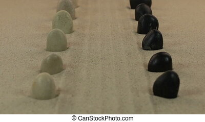 Approximation of two rows of white and black stones, lying on a lines from the sand.