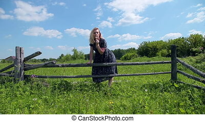 ?appy girl blowing on a dandelion and laughing in the background of a summer landscape near wooden fence.