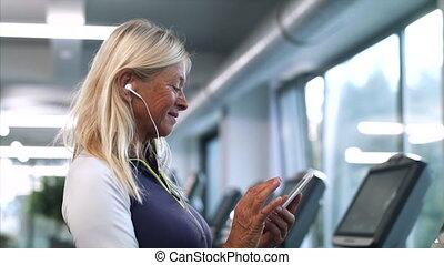 après, personne âgée femme, gymnase, exercise., reposer, smartphone