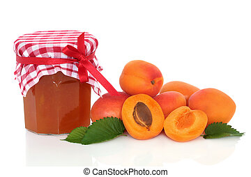 Apricot jam with fruit whole and in half with leaf sprigs, isolated over white background.