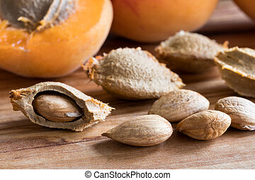 Apricot kernels and apricots on a wooden background
