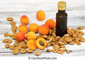 Apricot oil from apricot kernels in a brown bottle , apricot seeds around it and fresh apricots on wooden table
