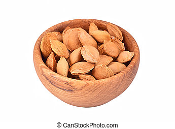 Apricot stone in wooden bowl on white background