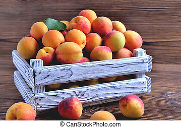 apricots in a white wooden box on a natural wooden brown background