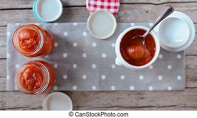 Apricots Marmalade Jars - Cinemagraph of hand placing jar...