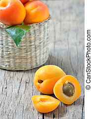 Apricots on the old wooden table and basket shoot in studio