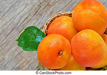 Apricots  on the old wooden table and basket
