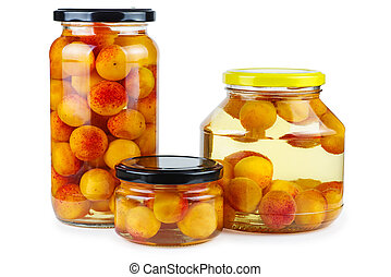 Apricots prepared and canned in glass jars isolated on white background