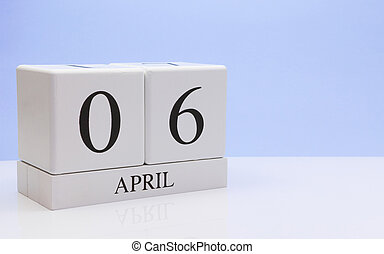 April 06st. Day 06 of month, daily calendar on white table with reflection, with light blue background. Spring time, empty space for text