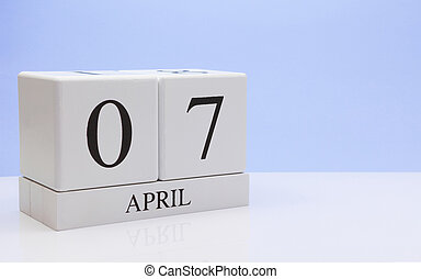 April 07st. Day 07 of month, daily calendar on white table with reflection, with light blue background. Spring time, empty space for text