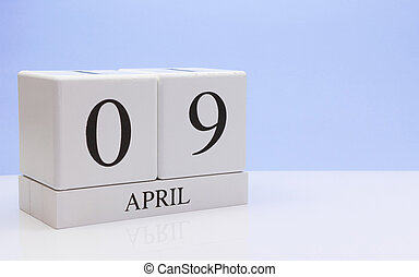 April 09st. Day 09 of month, daily calendar on white table with reflection, with light blue background. Spring time, empty space for text