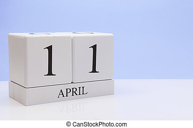 April 11st. Day 11 of month, daily calendar on white table with reflection, with light blue background. Spring time, empty space for text