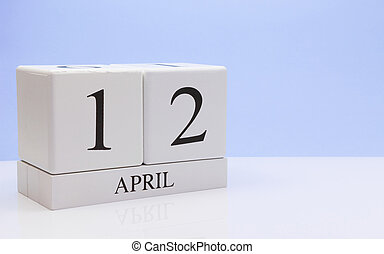 April 12st. Day 12 of month, daily calendar on white table with reflection, with light blue background. Spring time, empty space for text