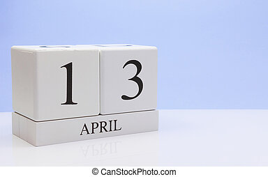 April 13st. Day 13 of month, daily calendar on white table with reflection, with light blue background. Spring time, empty space for text