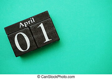 April 1st wooden calendar with space copy on green mint background