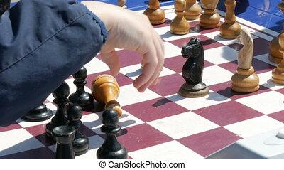 April 21, 2018 - Kamenskoye, Ukraine: Children play chess in the street. Street Chess Tournament outdoor, chess clock presses the hand