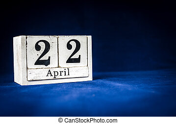 April 22nd, Twenty-second of April, Day 22 of month April - rustic wooden white calendar blocks on dark blue background with empty space for text