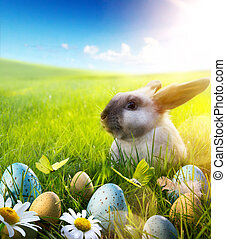 April Easter bunny; baby rabbit and easter eggs on spring flower