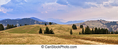 April evening in mountains. Spring hills and fields.