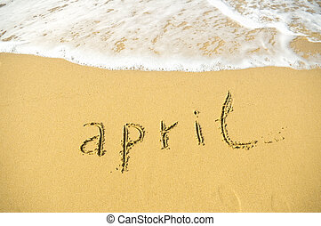 April - written in sand on beach texture