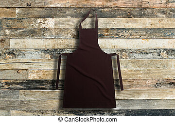 Apron - Brown apron against vintage wooden background or...