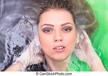 aqua tempting blond girl lying relaxing in the water looking at camera on green background closeup portrait