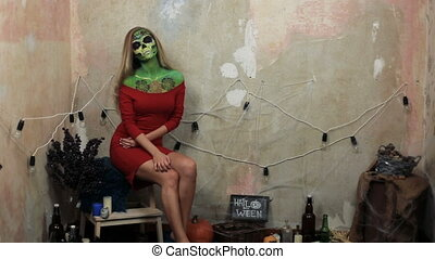 aquagrim face art on halloween tassels green scary glamorous rhinestones skeleton. Mexican Princess Sugar Skull. woman model posing in front of camera in red dress.