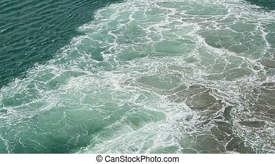 Aquamarine sea waves boil and foam from the working engine...