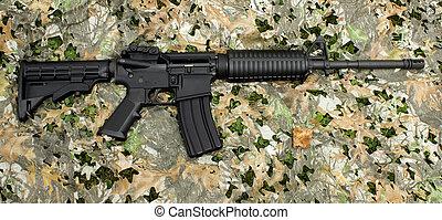 AR-15 rifle - An AR-15 rifle on a generic camouflage...