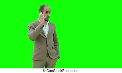 Arab business man talking on the mobile phone on a Green Screen, Chroma Key.
