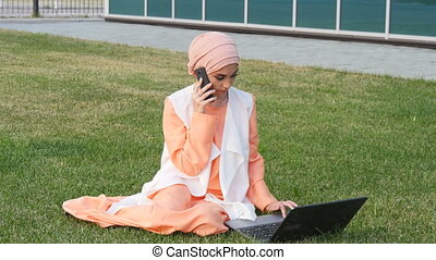 Arab business woman on the mobile phone in a park