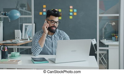 Arab businessman in casual clothing and glasses is talking on mobile phone and using laptop typing at work enjoying modern business and technology.