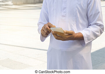 Arab businessman messaging on a mobile phone in the city