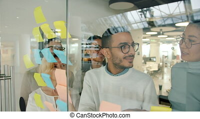 Arab businessman using glassboard with sticky notes sharing ...