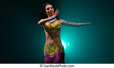 Arab dancer performs belly dance on stage. Smoke background....