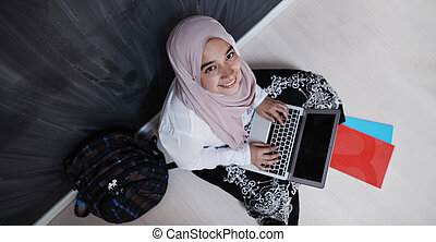 arab female student working on laptop from home