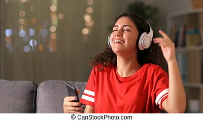 Arab girl dancing and listening to music at home