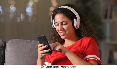 Happy arab girl wearing wireless headphones listening to music checking phone at home