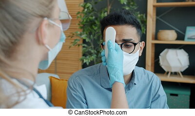 Arab man in face mask is talking to doctor at home checking body temperature coughing discussing corona virus infection symptoms and treatment.