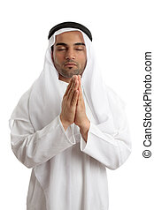 Arab man praying to God - Man wearing middle easter attire...