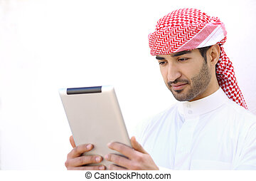 Arab man reading a tablet outdoor on white